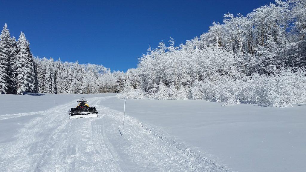 rime covered aspen trees and snowmobile grooming equipment in gold basin la sal mountain utah